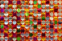 Texture of disk-shaped shiny metals bead sequins and spangles on a colorful decorative background royalty free stock photography