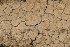 Texture of dry brown cracked earth. Lack of moisture on the soil, drought. The concept of dehydration land. Photo as wallpaper. royalty free stock photo