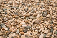 Texture of dry round colored sea pebbles on pebble beach, close-up. Pebbles stone background.  Small stones grave Royalty Free Stock Photos
