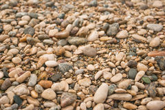 Texture of dry round colored sea pebbles on pebble beach, close-up. Pebbles stone background.  Small stones grave Stock Photography
