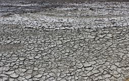 Texture of the earth`s surface and cracks next to the cold mud volcano. The layer of mud, which volcano erupts, quickly dries up royalty free stock photos