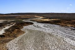 Texture of the earth`s surface and cracks next to the cold mud volcano. The layer of mud, which volcano erupts, quickly dries up stock images