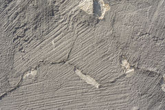 Texture of an embossed antique concrete wall with cracks and a ruined plaster protective layer Stock Photos
