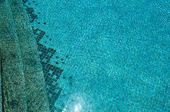 The texture of the entrance of the descent into the pool with blue water and square ceramic tiles on the steps. The background stock photography