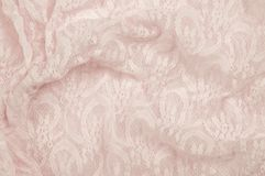 Texture, fabric, background. Lacy pink fabric, lace. A fine open. Fabric, typically one of cotton or silk, made by looping, twisting, or knitting in patterns Royalty Free Stock Image