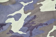 Texture of fabric with a camouflage painted in colors of the marsh. Army background image. Textile pattern of military camouflage. Fabric Royalty Free Stock Image