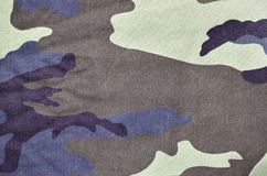 Texture of fabric with a camouflage painted in colors of the marsh. Army background image. Textile pattern of military camouflage. Fabric Royalty Free Stock Photography