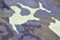 Texture of fabric with a camouflage painted in colors of the marsh. Army background image. Textile pattern of military camouflage. Fabric Royalty Free Stock Images