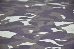 Texture of fabric with a camouflage painted in colors of the marsh. Army background image. Textile pattern of military camouflage. Fabric Royalty Free Stock Photo
