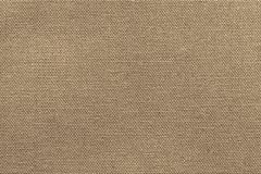 Texture fabric for a textile background of beige color. Rough texture of fabric or textile material for a background or for wallpaper of beige color Stock Photos