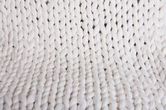 White plaid big knit. texture pigtail knitted blanket. The texture of fabric thick beige sweater close-up. Knitted texture background. white plaid big knit Royalty Free Stock Photo