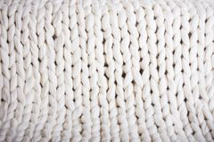 White plaid big knit. texture pigtail knitted blanket. The texture of fabric thick beige sweater close-up. Knitted texture background. white plaid big knit Stock Photo