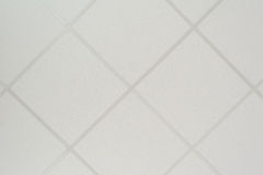 The texture of a false ceiling consisting of square plates and a directing profile of the diagonal arrangement. An abstract white background Stock Photo