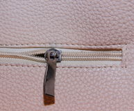 Texture faux leather with zipper. Beige-pink background with metal zip open halfway Royalty Free Stock Images