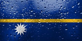 Texture of flag of Nauru. Texture of Nauru flag on the glass with drops of rain stock photo