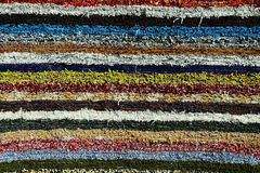 Texture of fluffy handmade carpet produced on hand-loom, pattern of various colorful vertical lines Royalty Free Stock Photos