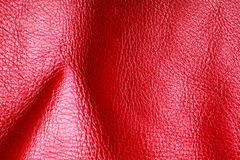Texture of folds vivid red skin leather background. Red leather texture background closeup. Folds wavy natural skin material Stock Photos