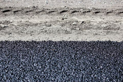 Texture of fresh hot black asphalt is laid on the new road near the roadside and car track.  Royalty Free Stock Image
