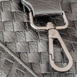 Texture of genuine dark wicker leather close-up and clasp, buckle of male handbag. Concept of shopping, manufacturing. Texture of genuine dark wicker leather Royalty Free Stock Images