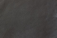 Texture of genuine leather close-up, cowhide. Black color. For natural, artisan backgrounds, substrate composition use. Texture of genuine leather close-up Stock Photos