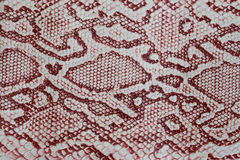 Texture of genuine leather close-up, embossed under the skin a reptile, with fashion pattern and matte surface. Claret Royalty Free Stock Images
