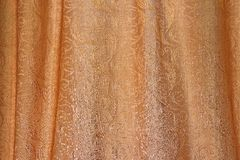 Texture of gold fabric with pleats and abstract ornament Royalty Free Stock Images