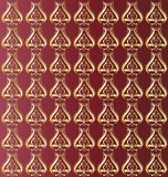 Texture gold pattern. On a red background gold ornament in the form of weaving Royalty Free Stock Images