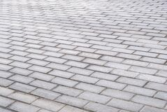 Texture of gray patterned paving tiles on the ground of street, perspective view. Concrete paving slab flagstone. Cement brick