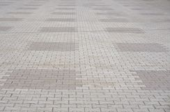Texture of gray and yellow patterned paving tiles on the ground of street, perspective view. Cement brick squared stone floor back. Ground. Concrete paving slab royalty free stock photography