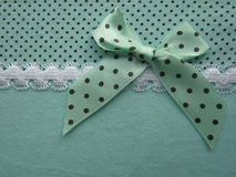 Texture of green fabric dots with white lace large with a bow Royalty Free Stock Images