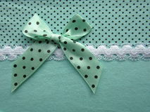 Texture of green fabric dots with white lace large with a bow Stock Image
