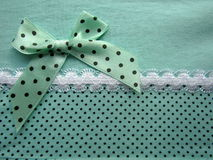 Texture of green fabric dots with white lace large with a bow Stock Photos