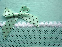 Texture of green fabric dots with white lace large with a bow Stock Images