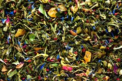 Texture of green tea with dried petals of blue flowers, calendula, cornflower. Food background. Organic healthy herbal. Leaves, detox tea Stock Photos