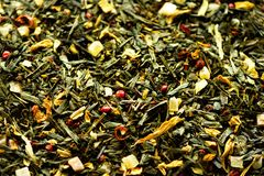 Texture of green tea with dried petals yellow flowers and red pepper. Food background. Organic healthy herbal leaves. Detox tea Stock Photography
