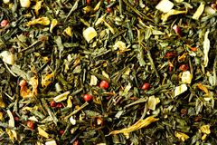 Texture of green tea with dried petals yellow flowers and red pepper. Food background. Organic healthy herbal leaves. Detox tea Royalty Free Stock Photography