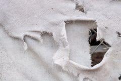 Texture grunge déchirée grise blanche sale de fond de toile de tissu de vintage, avec le maillon de chaîne vu par un trou photos libres de droits