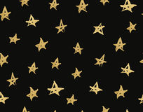 Texture with hand drawn stars. Seamless pattern with gold stars on a black background. Royalty Free Stock Image
