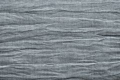 Texture of horizontally crumpled knitted fabric. Texture crumpled knitted fabric of white gray silvery color Royalty Free Stock Photography
