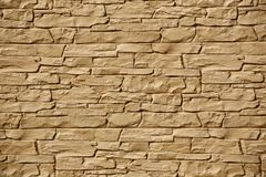 Texture of an irregular fieldstone wall in sunlight.  Royalty Free Stock Images