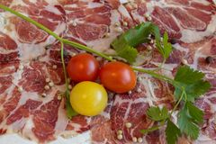 Texture of Italian delicacy dried meat with spices, cherry tomatoes and sprig of parsley. The different shades of red and white with several accents in yellow Royalty Free Stock Photography