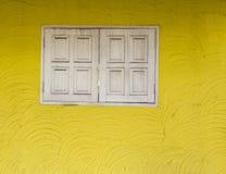 Texture jaune de mur de ciment et vieille fenêtre en bois blanche Photo libre de droits
