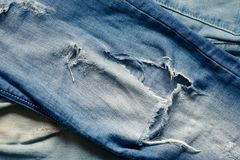 Texture of jeans material with a hole. Texture of blue jeans material with a hole Royalty Free Stock Photo