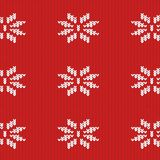 Texture of a knitted red fabric with a white pattern. In the form of snowflakes Royalty Free Stock Images