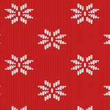 Texture of a knitted red fabric with a white pattern. In the form of snowflakes Royalty Free Stock Photo