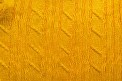 The texture of a knitted woolen fabric. Background to create a winter layouts, Christmas cards, banners. Knit yellow sweater. Stock Images