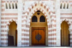Texture of large beautiful wooden doors of an Arab Muslim Islamic temple made of white and brown bricks with arches for prayers. T royalty free stock photos