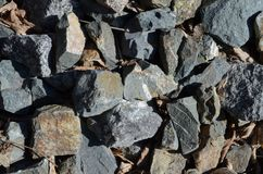 The texture of large stones under the sun: blue, rusty, jet color royalty free stock image