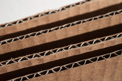Texture of layered brown cardboard side. Folded cardboard boxes stock images