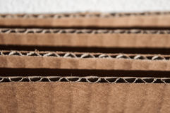 Texture of layered brown cardboard side. Folded cardboard boxes. Stock Images